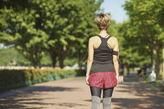 Mujer asiática joven que camina en parque de la ciudad después de activar Fotos de archivo