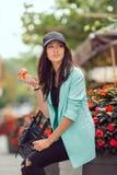 Mujer asiática joven que come los alimentos de preparación rápida al aire libre Imagen de archivo libre de regalías