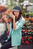 Mujer asiática joven que come los alimentos de preparación rápida al aire libre Imagenes de archivo