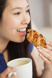 Mujer asiática joven que come pasteles con una taza de café Foto de archivo