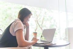 Mujer asiática joven que comprueba el correo electrónico en el ordenador portátil y el pensamiento Fotos de archivo libres de regalías