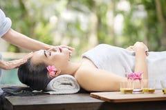 Mujer asiática joven que consigue el tratamiento de la cara de la piel imagenes de archivo