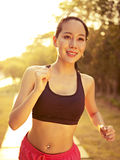 Mujer asiática joven que corre en parque Foto de archivo