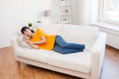 Mujer asiática joven que duerme en el sofá en casa Imagen de archivo
