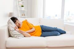 Mujer asiática joven que duerme en el sofá en casa Foto de archivo