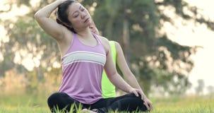 Mujer asiática joven que ejercita en parque en día hermoso