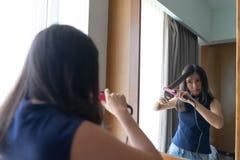 Mujer asiática joven que endereza el pelo con el whil de la enderezadora del pelo foto de archivo libre de regalías