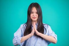 Mujer asiática joven que gesticula en actitudes defferent sobre backgro azul Foto de archivo