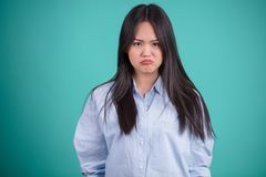 Mujer asiática joven que gesticula en actitudes defferent sobre backgro azul Fotos de archivo libres de regalías