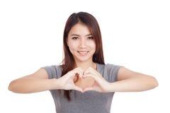 Mujer asiática joven que gesticula la muestra de la mano del corazón Foto de archivo libre de regalías