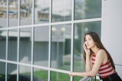 Mujer asiática joven que habla en smartphone cerca de la pared de cristal Imagen de archivo libre de regalías