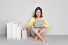 Mujer asiática joven que hace compras en línea en casa sentándose además de fila de Fotos de archivo libres de regalías