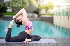 Mujer asiática joven que hace ejercicio de la yoga cerca de piscina Fotos de archivo