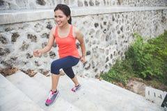 Mujer asiática joven que hace el ejercicio al aire libre en un parque, activando para arriba Foto de archivo libre de regalías