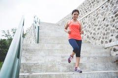 Mujer asiática joven que hace el ejercicio al aire libre en un parque, activando para arriba Imagen de archivo