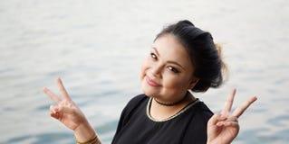 Mujer asiática joven que hace la muestra de la mano de V Foto de archivo libre de regalías