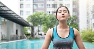 Mujer asiática joven que hace movimientos de la yoga o que medita por la piscina, Imágenes de archivo libres de regalías