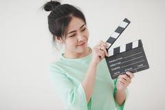 Mujer asiática joven que juega clapperboard con la emoción positiva Foto de archivo libre de regalías