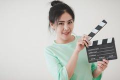 Mujer asiática joven que juega clapperboard con la emoción positiva Imagen de archivo libre de regalías
