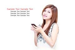 Mujer asiática joven que juega en su teléfono móvil Imagen de archivo
