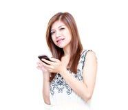 Mujer asiática joven que juega en su teléfono móvil Imagenes de archivo