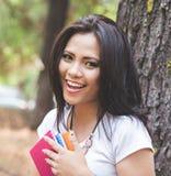 Mujer asiática joven que lee un libro al aire libre en un parque Imágenes de archivo libres de regalías