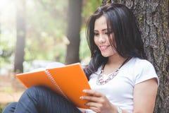 Mujer asiática joven que lee un libro al aire libre en un parque Fotografía de archivo libre de regalías