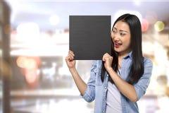Mujer asiática joven que lleva a cabo el tablero de la muestra con el espacio vacío Foto de archivo