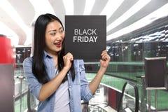 Mujer asiática joven que lleva a cabo el tablero de la muestra con el texto de Black Friday Imágenes de archivo libres de regalías