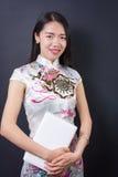Mujer asiática joven que lleva a cabo un dispositivo del ordenador portátil fotos de archivo libres de regalías
