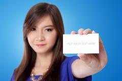 Mujer asiática joven que muestra una tarjeta blanca en blanco Foto de archivo libre de regalías