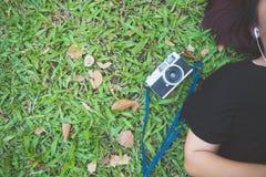 Mujer asiática joven que pone en la hierba verde que escucha la música en el parque con una emoción desapasible Fotos de archivo libres de regalías