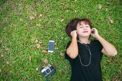Mujer asiática joven que pone en la hierba verde que escucha la música en el parque con una emoción desapasible Imagen de archivo libre de regalías