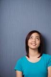Mujer asiática joven que se coloca que sueña despierto Fotografía de archivo libre de regalías