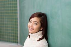 Mujer asiática joven que se inclina en una pizarra vacía Foto de archivo libre de regalías