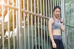 Mujer asiática joven que se relaja después de activar el soporte del ejercicio contra el acero en parque para refrescar su cuerpo Imagen de archivo