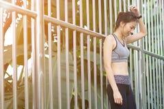 Mujer asiática joven que se relaja después de activar el soporte del ejercicio contra el acero en parque para refrescar su cuerpo Fotos de archivo libres de regalías