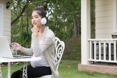 Mujer asiática joven que se sienta en la silla que escucha la música y usar imagenes de archivo