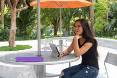 Mujer asiática joven que se sienta en la tabla al aire libre con la tableta Fotografía de archivo libre de regalías
