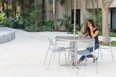 Mujer asiática joven que se sienta en la tabla al aire libre con la tableta Imagen de archivo libre de regalías