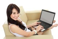 Mujer asiática joven que se sienta en sofá usando un ordenador portátil Imágenes de archivo libres de regalías