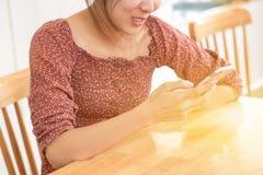 Mujer asiática joven que se sienta en una tabla usando el teléfono móvil Smart p Imagen de archivo libre de regalías