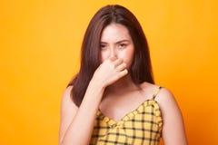 Mujer asiática joven que se sostiene la nariz debido a un mún olor imagenes de archivo