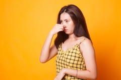 Mujer asiática joven que se sostiene la nariz debido a un mún olor fotografía de archivo