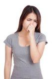 Mujer asiática joven que se sostiene la nariz debido a un mún olor imágenes de archivo libres de regalías