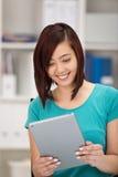 Mujer asiática joven que sonríe como ella lee su tableta Imágenes de archivo libres de regalías