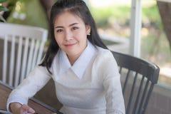 Mujer asiática joven que sonríe mientras que se sienta en café Fotos de archivo libres de regalías