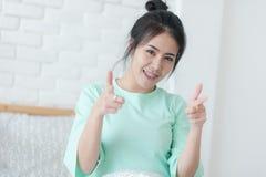 Mujer asiática joven que sonríe mientras que se sienta en cama foto de archivo