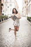 Mujer asiática joven que sonríe y que muestra a clapperboard escena urbana Foto de archivo