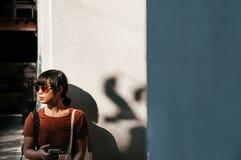 Mujer asiática joven que sostiene el teléfono móvil bajo luz del sol con blanco Fotografía de archivo